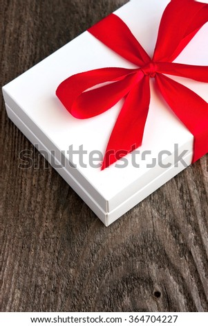 Valentines Day gift box with curved ribbon on old wood. Holiday background