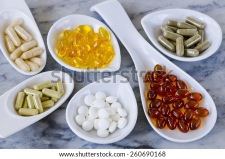 Variety of dietary supplements, including capsules of Garlic, Evening Primrose Oil; Artichoke Leaf;  Olive Leaf; Magnesium and Omega 3 Fish Oil.Selective focus. Taken in daylight. - stock photo