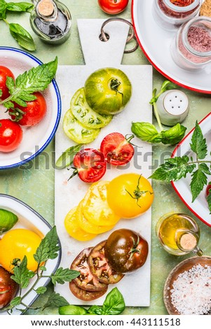 .Various Colorful sliced tomatoes on white marble cutting board with salad cooking ingredients,  preparation on kitchen table, top view. Healthy eating concept - stock photo