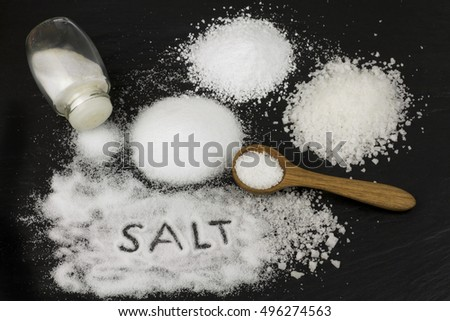Various salts and wooden spoon on black stone background.
