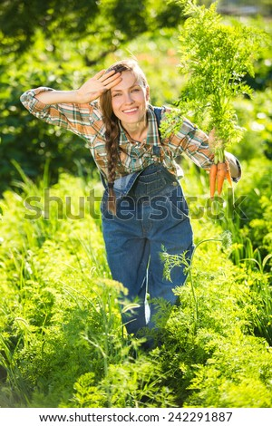 Vegetable garden - lovely gardener with bunch of carrots. focus on face, backlight
