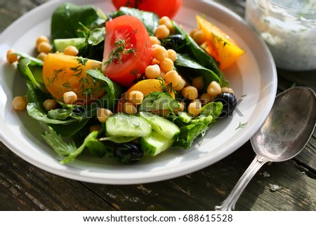 vegetables salad with chick pea, food on rustic boards