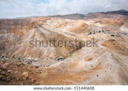 Vicinities of an ancient fortress Masada and a foot track on its slope, Israel - stock photo