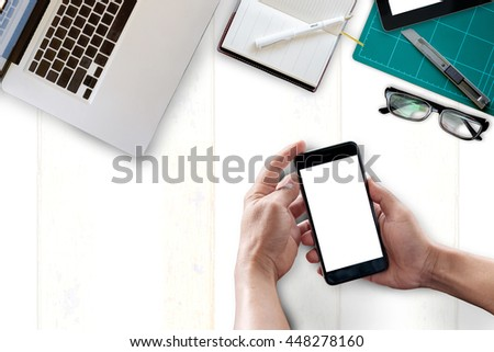 View from above.Office desk background with hands holding blank screen of mobile phone.  - stock photo