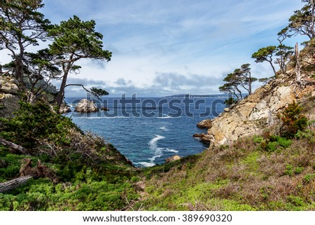 View of Carmel Bay, on a crisp spring morning, Cypress trees, blue sea & sky, & unusual rock and geological formations, as seen from the North Shore Trail, at Point Lobos State Natural Reserve - stock photo