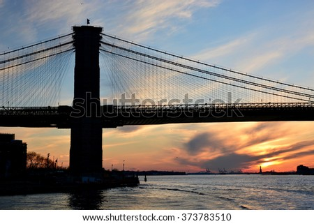 View of New York City Brooklyn bridge and manhattan bridge in Manhattan during sunset taken from a boat/ View of the sunset at New York City Brooklyn bridge - stock photo