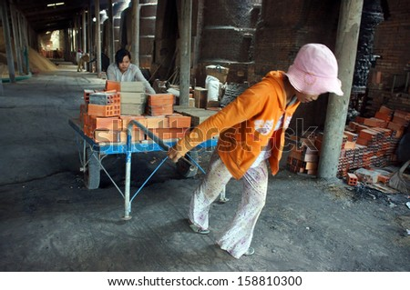 VINH LONG, VIET NAM- JULY 1: Worker working at brick factory, workwoman in hard work, pulling up the rickshaw with full of brick in Vinh Long, Viet Nam on July 1, 2013