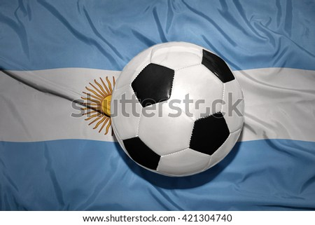 vintage black and white football ball on the national flag of argentina - stock photo