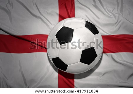 vintage black and white football ball on the national flag of england - stock photo