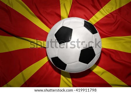vintage black and white football ball on the national flag of macedonia