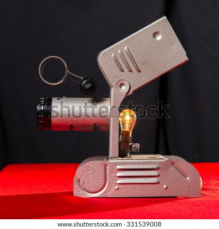 vintage movie spotlight on red table and black background  - stock photo