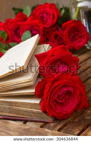 vintage old book  on table with red roses - stock photo