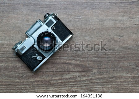 vintage photo camera  on a wooden background - stock photo