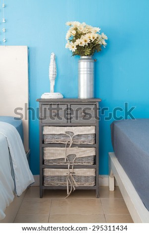vintage style wood cabinet and basket put in bedroom with decorated flowers. - stock photo