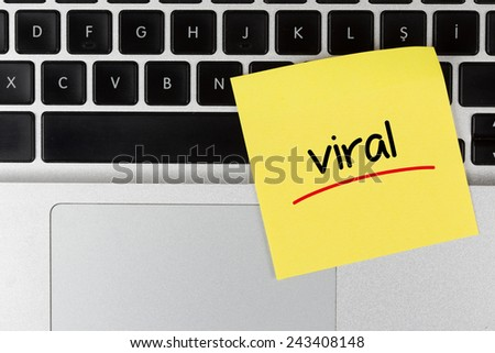 """Viral"" Written on Sticky Note on Laptop Keyboard - stock photo"