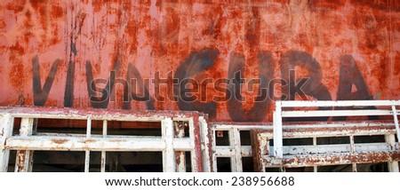 """Viva Cuba"" painted on a wall in Havana location - Old Havana, Cuba date - April 7, 2014 factual description - ""Viva Cuba"" painted on a red wall partially covered by unused window frames. - stock photo"
