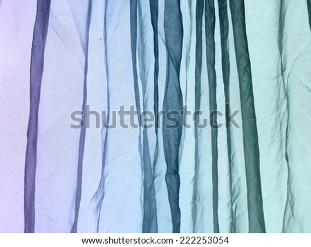 Voile curtain fading colors purple to blue to green background   - stock photo