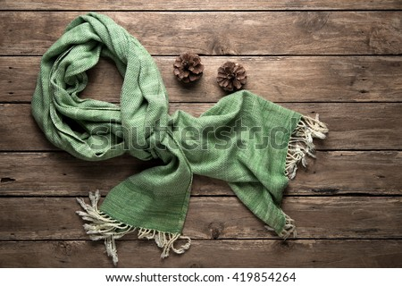 warm scarf on rustic with pine corn wooden background. Top view  - stock photo
