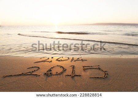 2014 washed away by a wave from the sea, 2015 begins. a new year starts - stock photo