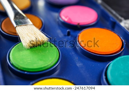 watercolor paints in a box with paintbrush - stock photo
