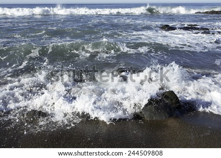 Waves crushing on a rocky beach making sea foam on Moonstone Beach. California Central Coast, near Cambria CA - stock photo