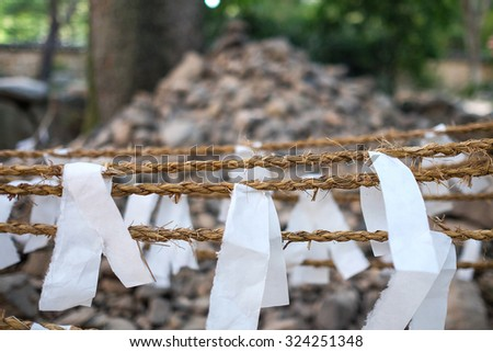 Way to make a wish in Korea. They will ribbon the white paper with the rope and stack uo the rock to make a wishing.  - stock photo