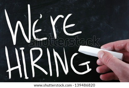 """We are hiring!"" handwritten with white chalk on a blackboard - stock photo"