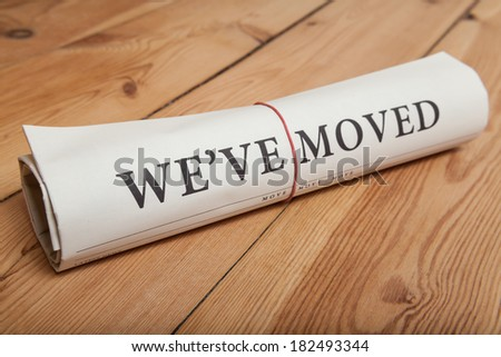 """we've moved"" newspaper on wooden floor - stock photo"