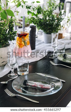 Wedding table decorated with candles, served with cutlery and crockery and covered with a tablecloth. Banquet dinner party with magic gift on plate