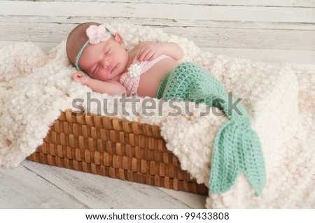 2 week old newborn girl wearing a crocheted mermaid costume, sleeping in a basket with a bleached wood background. - stock photo