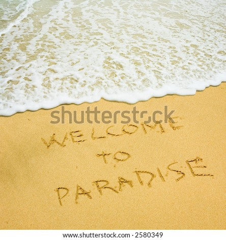"""welcome to paradise"" written in the sandy beach - stock photo"