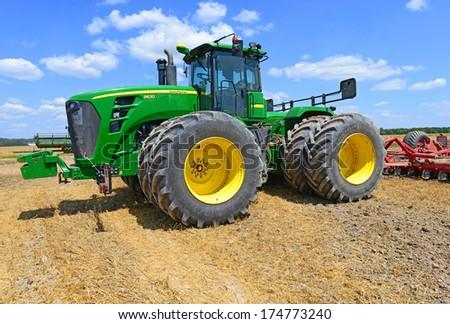 09.07.2013. Western Ukraine, near the town Kalush. Modern John Deere tractor. - stock photo