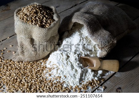 Wheat and Flour in Jute Bags on an Old Wooden Table Over Black Background, Closeup - stock photo