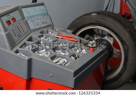 Wheel Balancing, Technician spins a car wheel as he waits for the machine to tell him he's reached the right spot to add a balancing weight. - stock photo