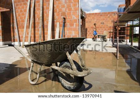wheelbarrow on construction site.  Worker on background. - stock photo