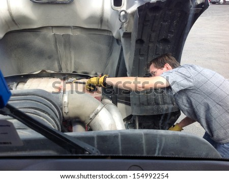18-Wheeler Pre-trip Tire Inspection - A professional driver is under the hood of his semi truck prior to driving OTR. - stock photo