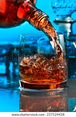 whiskey and ice on a glass table - stock photo