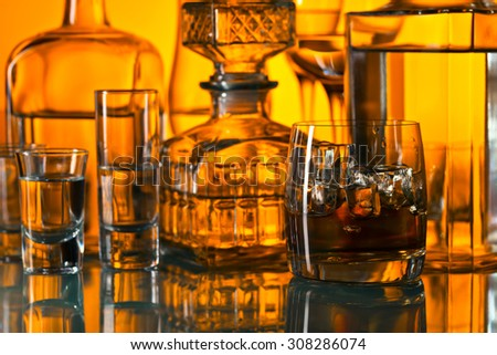 whiskey with ice in bar on glass table  - stock photo