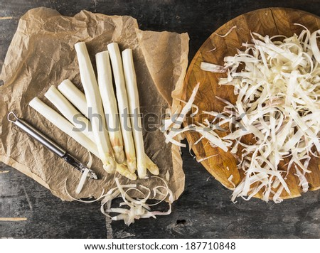 white asparagus with peelings on brown crumpled paper with knife - stock photo