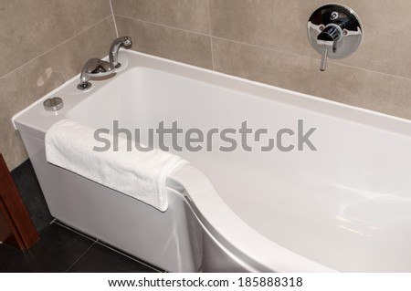white bathtub in the bathroom with a towel