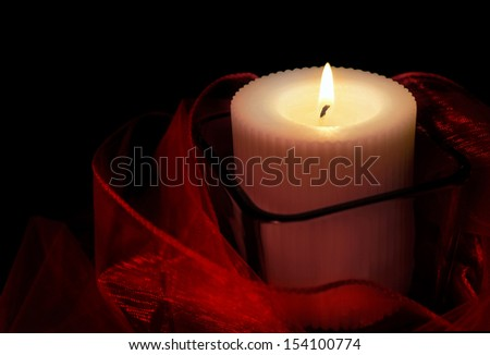 White candle in a glass holder with a red sash.                               - stock photo