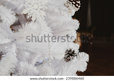 white Christmas tree with pine cones, beads and balls closeup