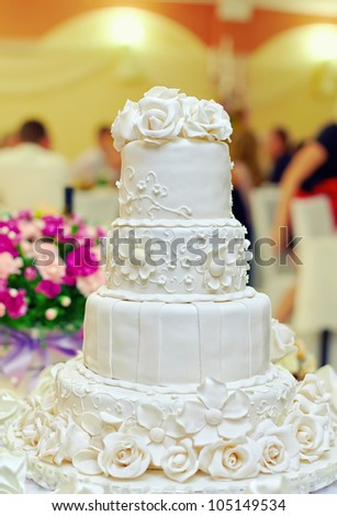 white floral wedding cake on restaurant interior background - stock photo