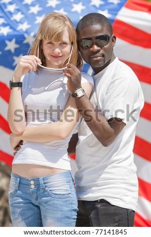 White girl and black guy outdoors. White girl and black guy on background of American flag - stock photo