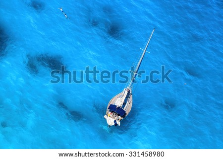 White luxury yacht against azure sea with swimming people - stock photo