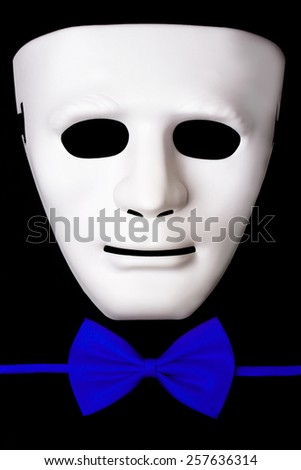 White mask and blue bow tie isolated on black background