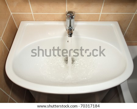 White modern ceramic handbasin and chrome tap, water running. - stock photo