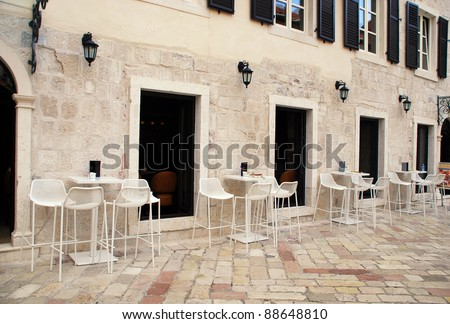 white tables and chairs at a sidewalk cafe in old mediterranean town (Italy) - stock photo