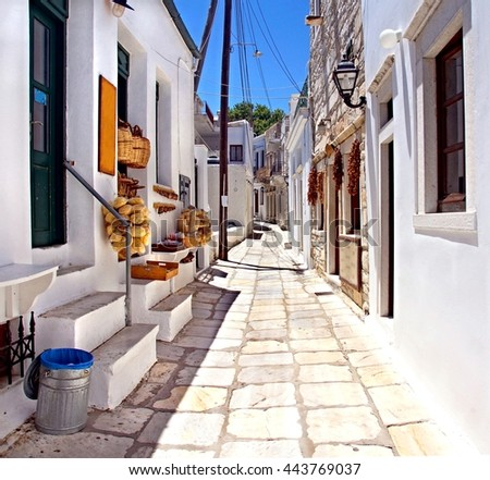 white washed picturesque Sunny alley at the Cyclades Island of Naxos , Greece