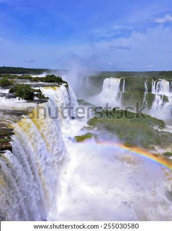 White whipped foam of water and a thin mist over the water.  Magnificent rainbow shines in the mist. The most high-water waterfall in the world - Iguazu. The picture is taken by lens Fisheye - stock photo